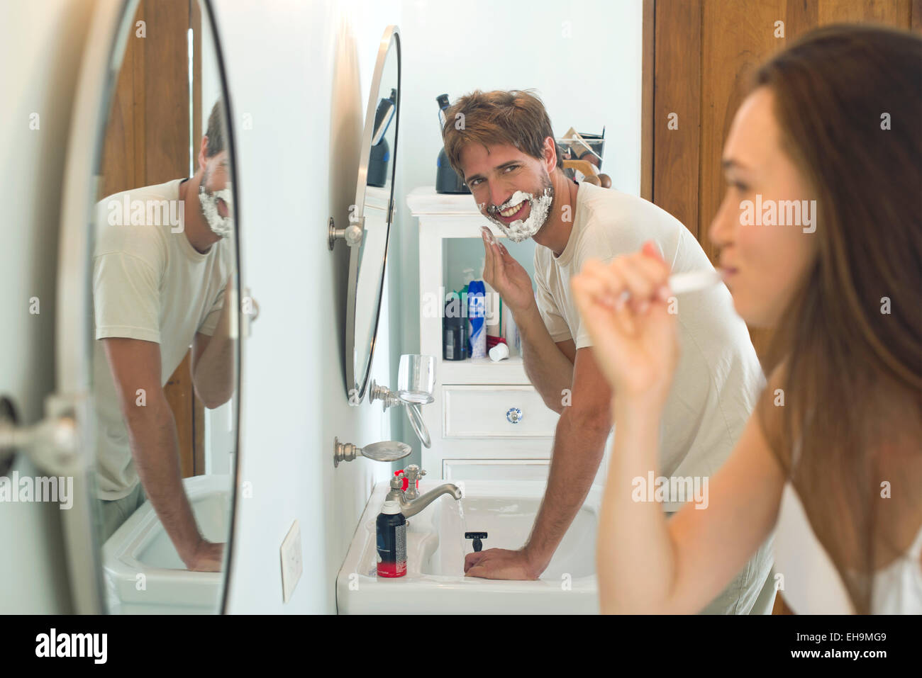 Woman brushing teeth, husband shaving - Stock Image