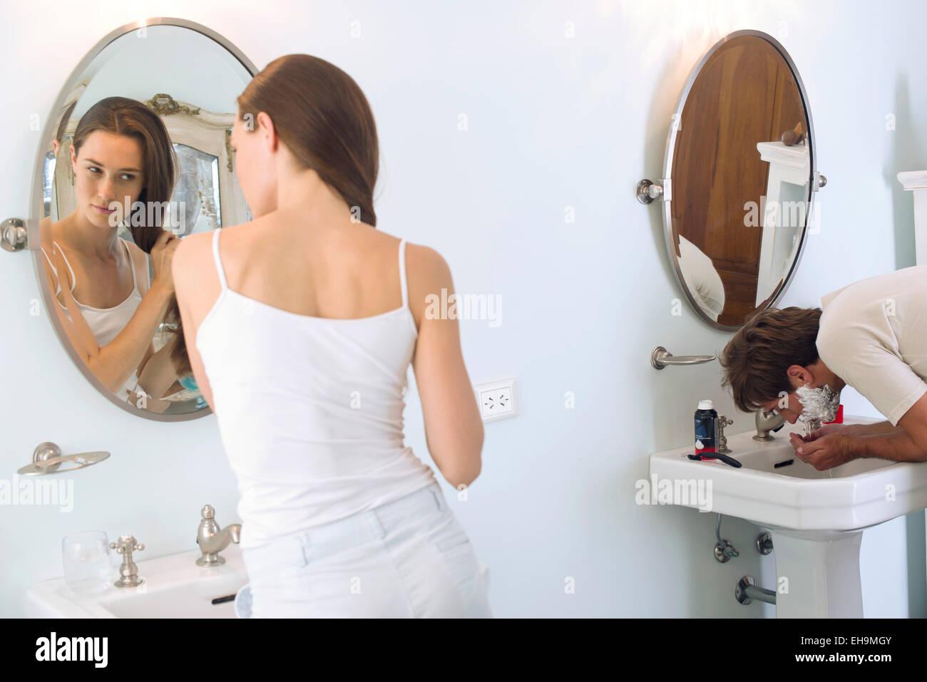 Woman brushing hair, husband shaving - Stock Image