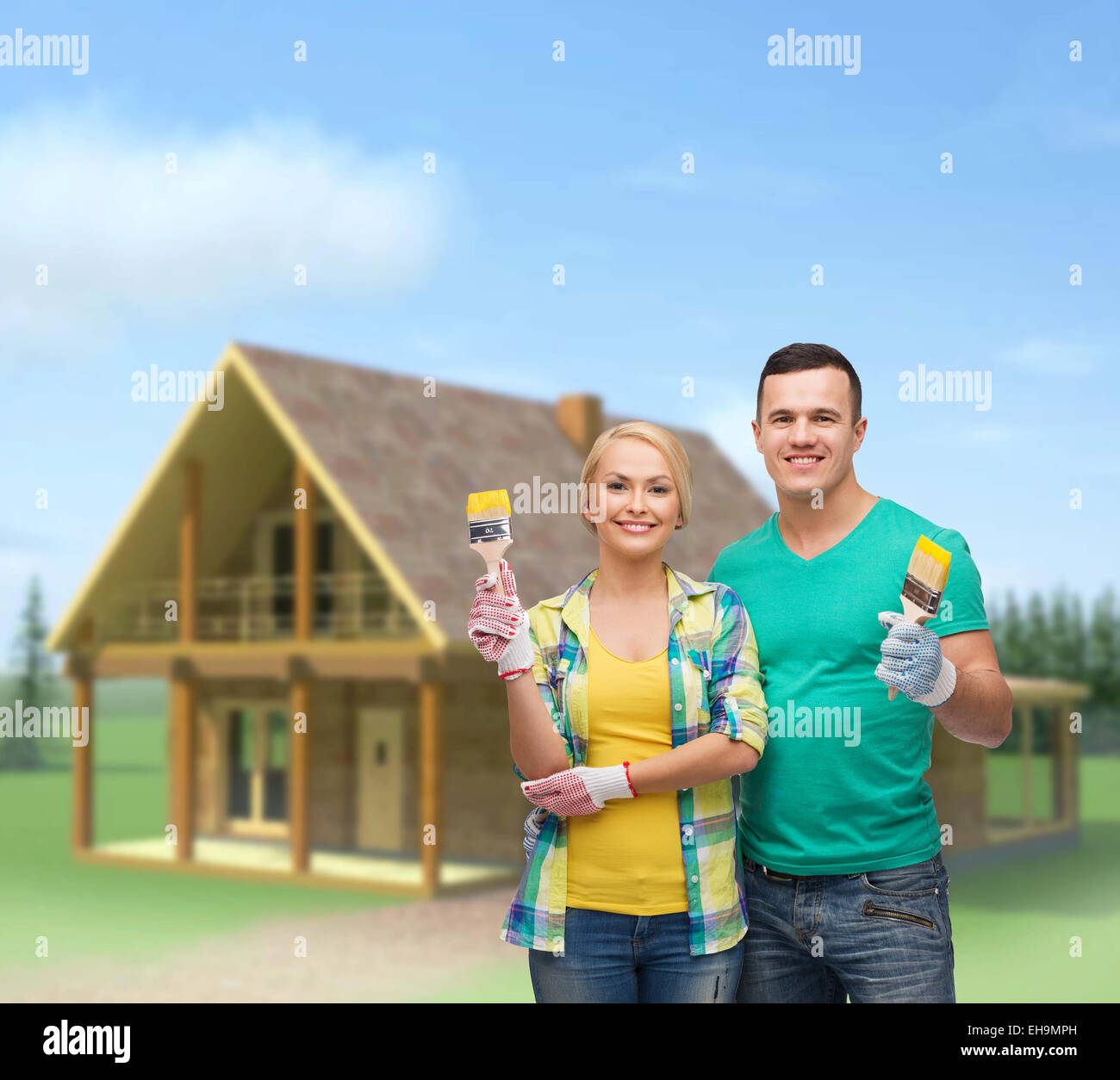 smiling couple with paintbrush - Stock Image