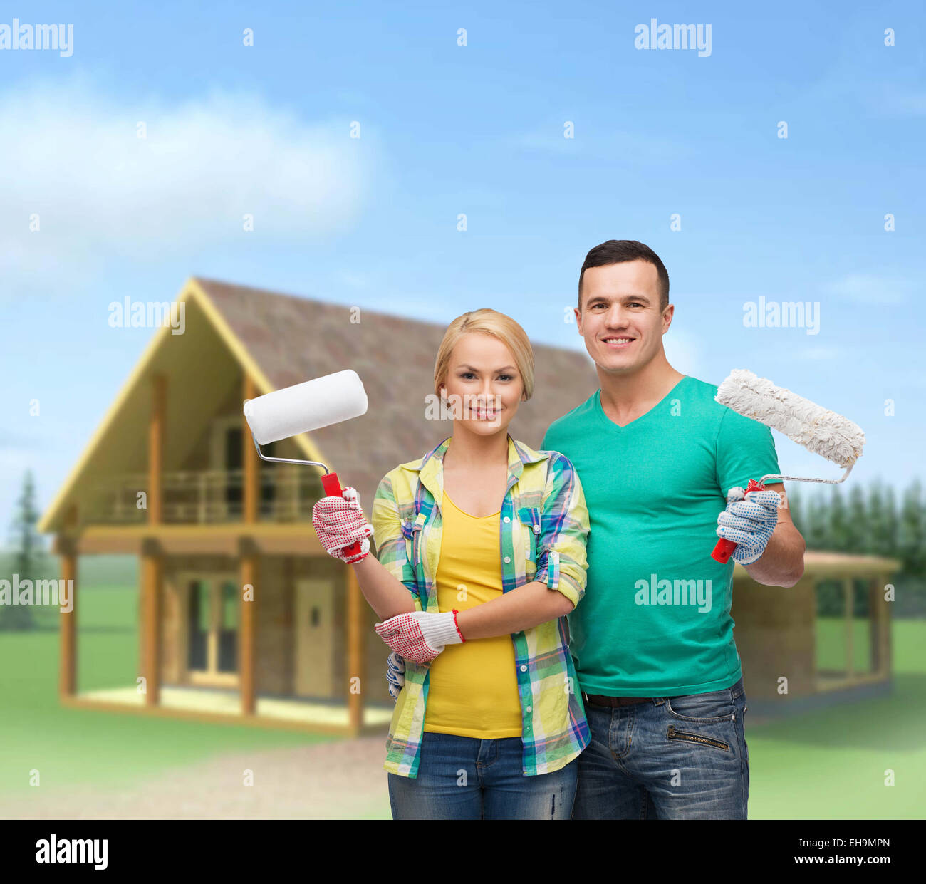 smiling couple in gloves with paint rollers - Stock Image