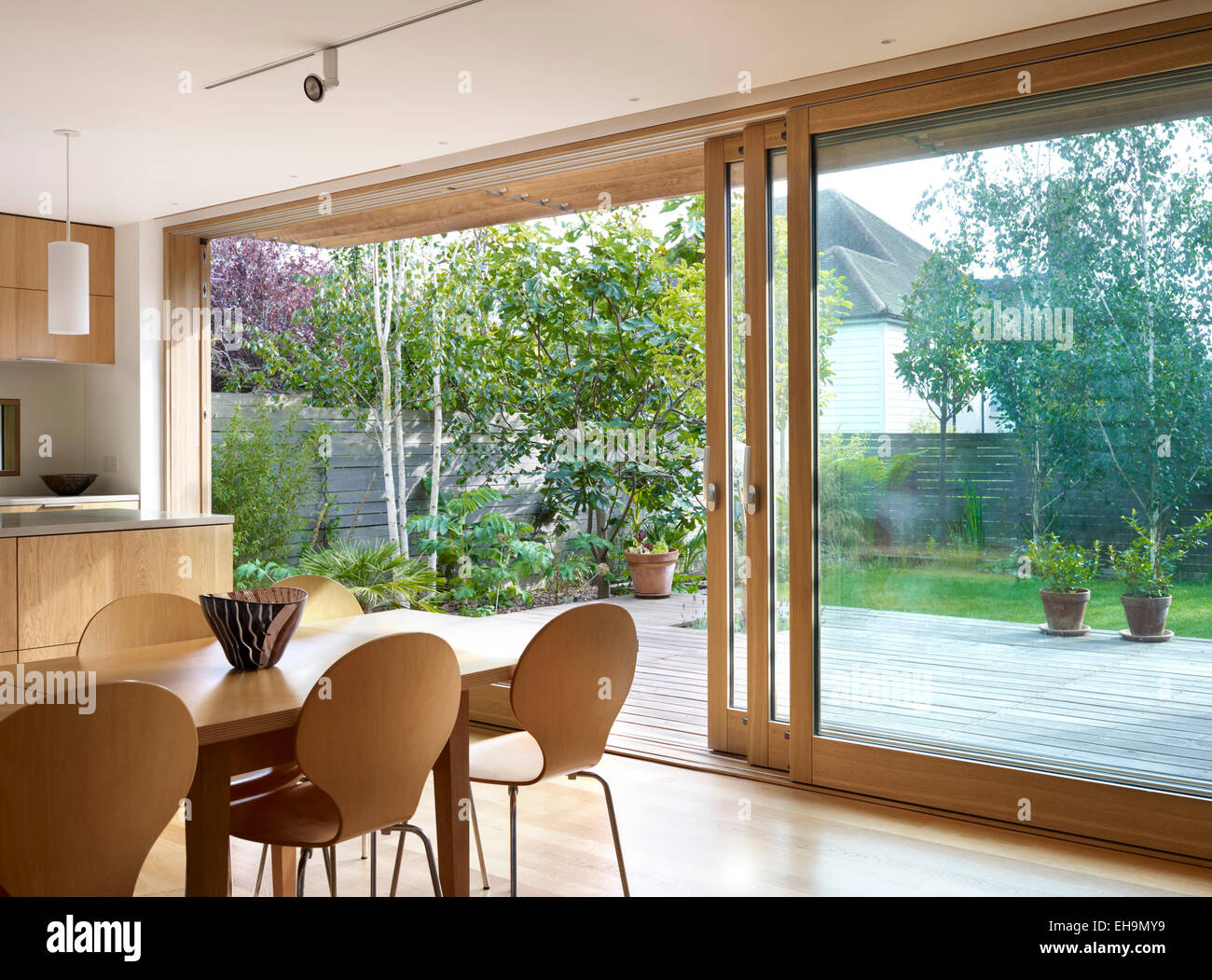 Wooden Dining Table And Chairs In Front Of Large Sliding Glass Doors Residential House Lloyd Close UK