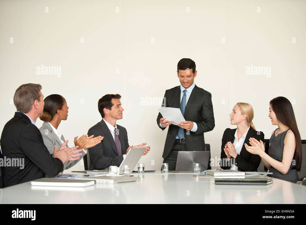 Businesspeople applauding at meeting - Stock Image