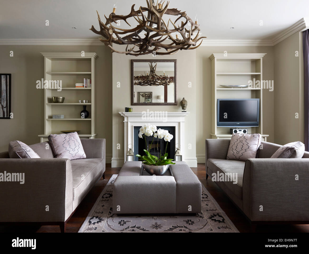 Modern lounge with sofas bookshelves and antler lighting fixture with reflection in mounted mirror in stevenage road home uk