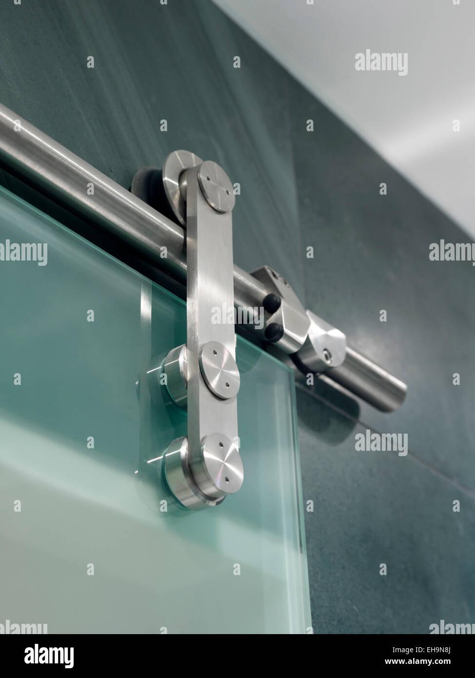Close up of metal fixture of glass sliding door in bathroom of ...