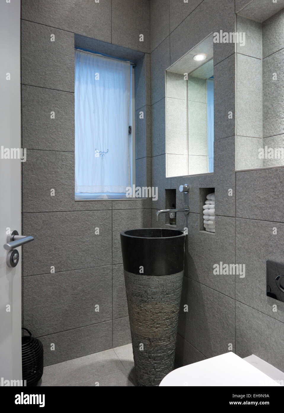 Modern sculpted marble hand basin in stone tiled toilet room in Cumberland Street home, UK - Stock Image