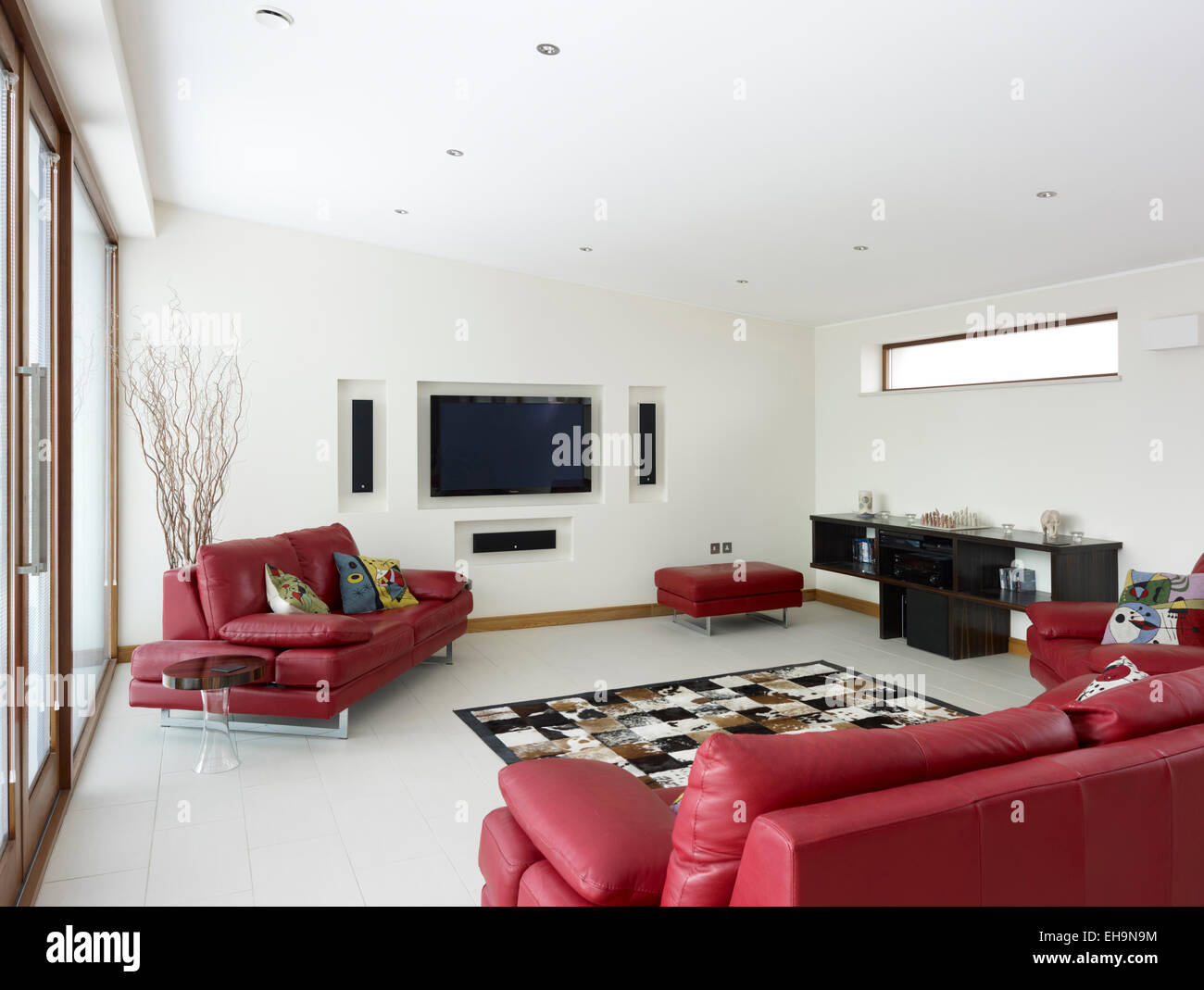 Modern living room with red leather sofas and built in plasma TV and ...