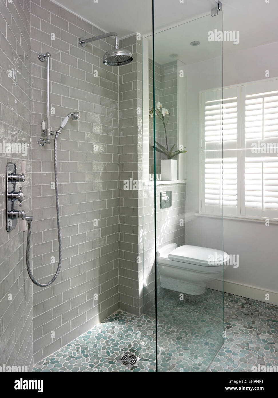 Beige Tiled Shower Room With Natural Pebble Floor With Toilet In Fernhurst  Road Home, UK