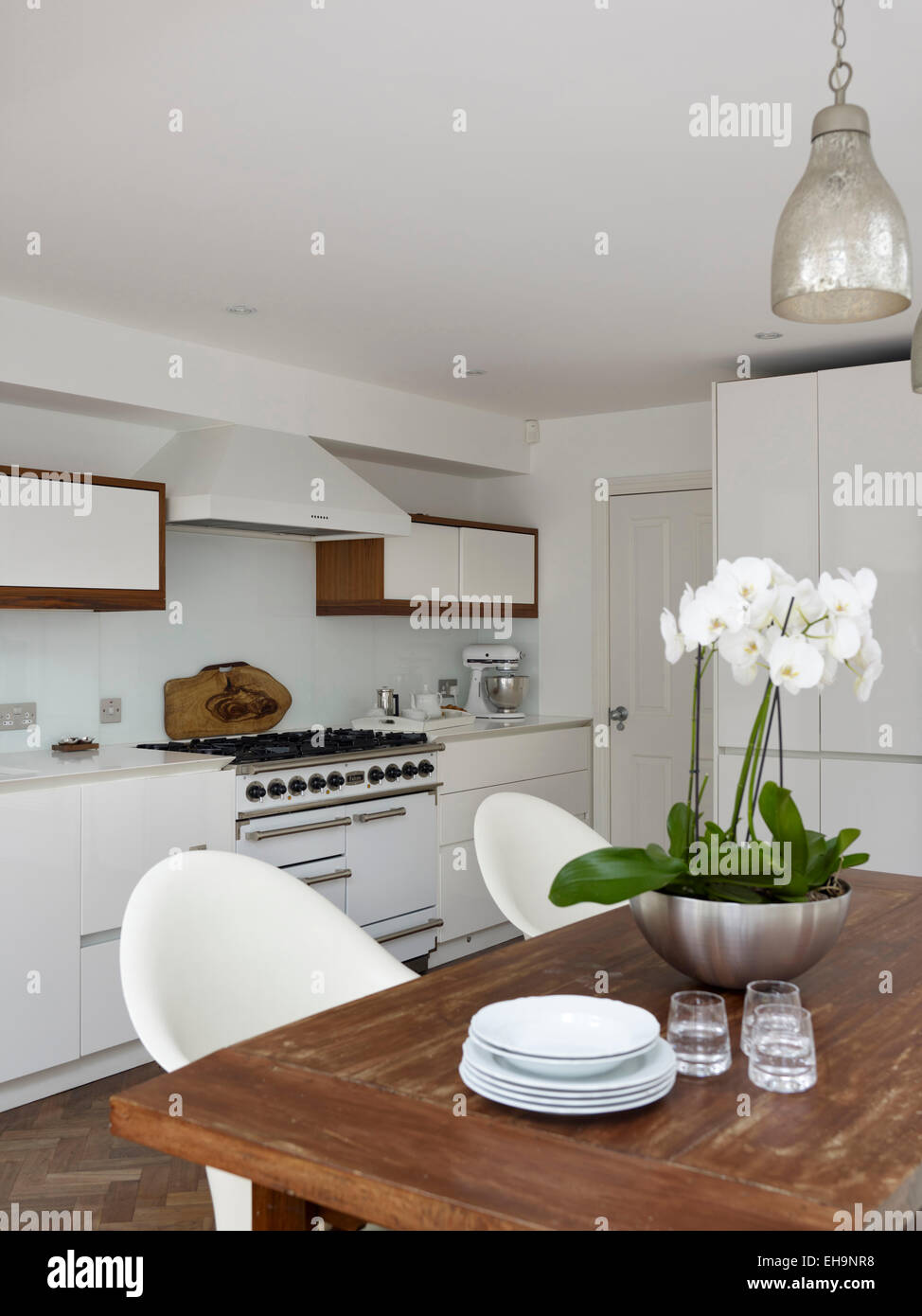 orchid on wooden table with pendant lighting in modern kitchen of