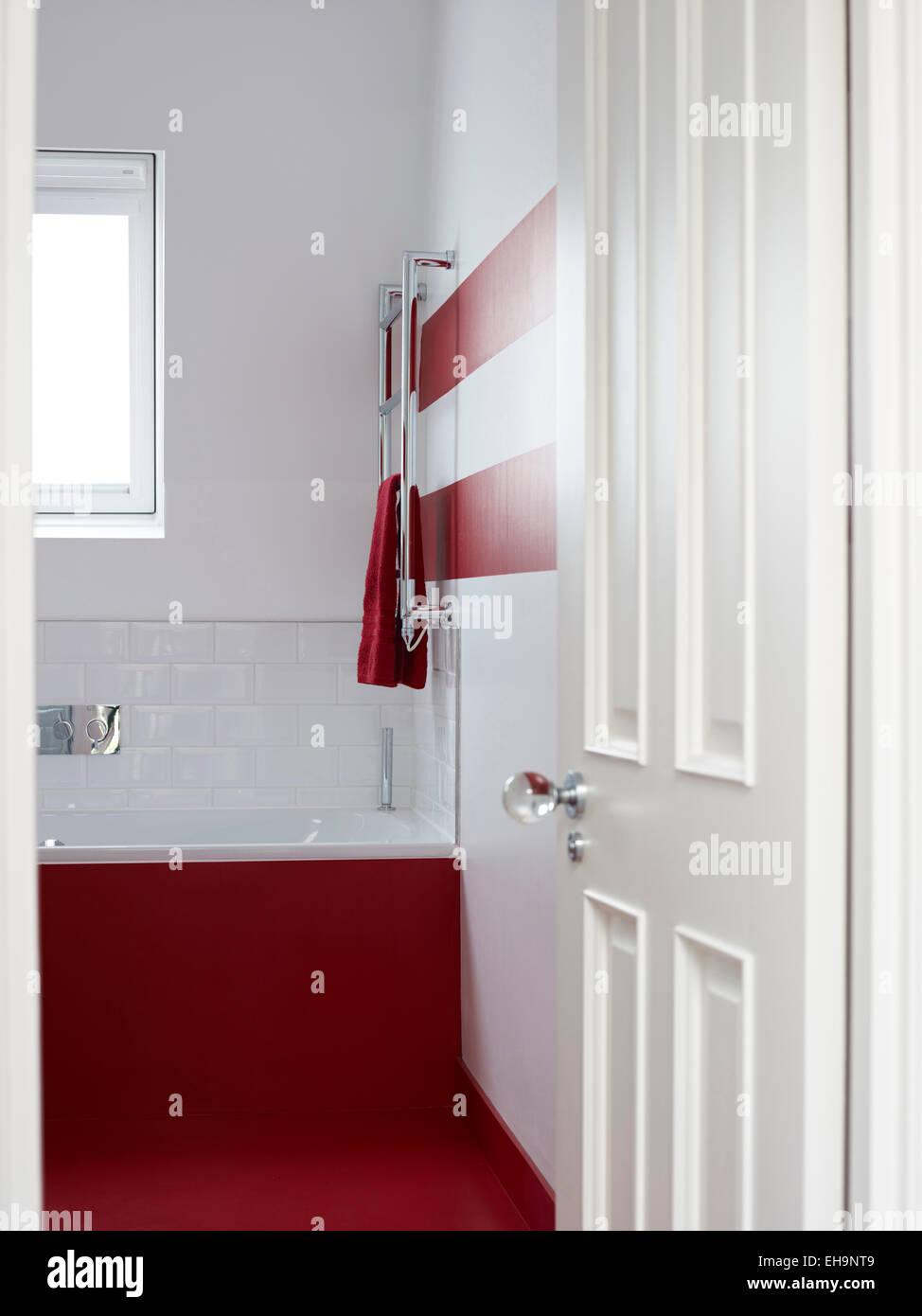 View through open door to red painted bathroom with metallic towel ...