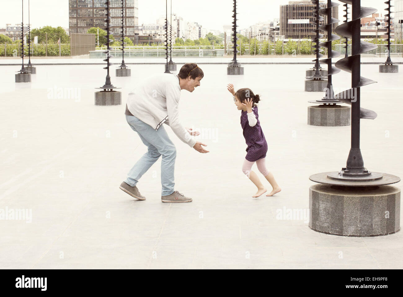 Father and daughter playing together in urban park - Stock Image
