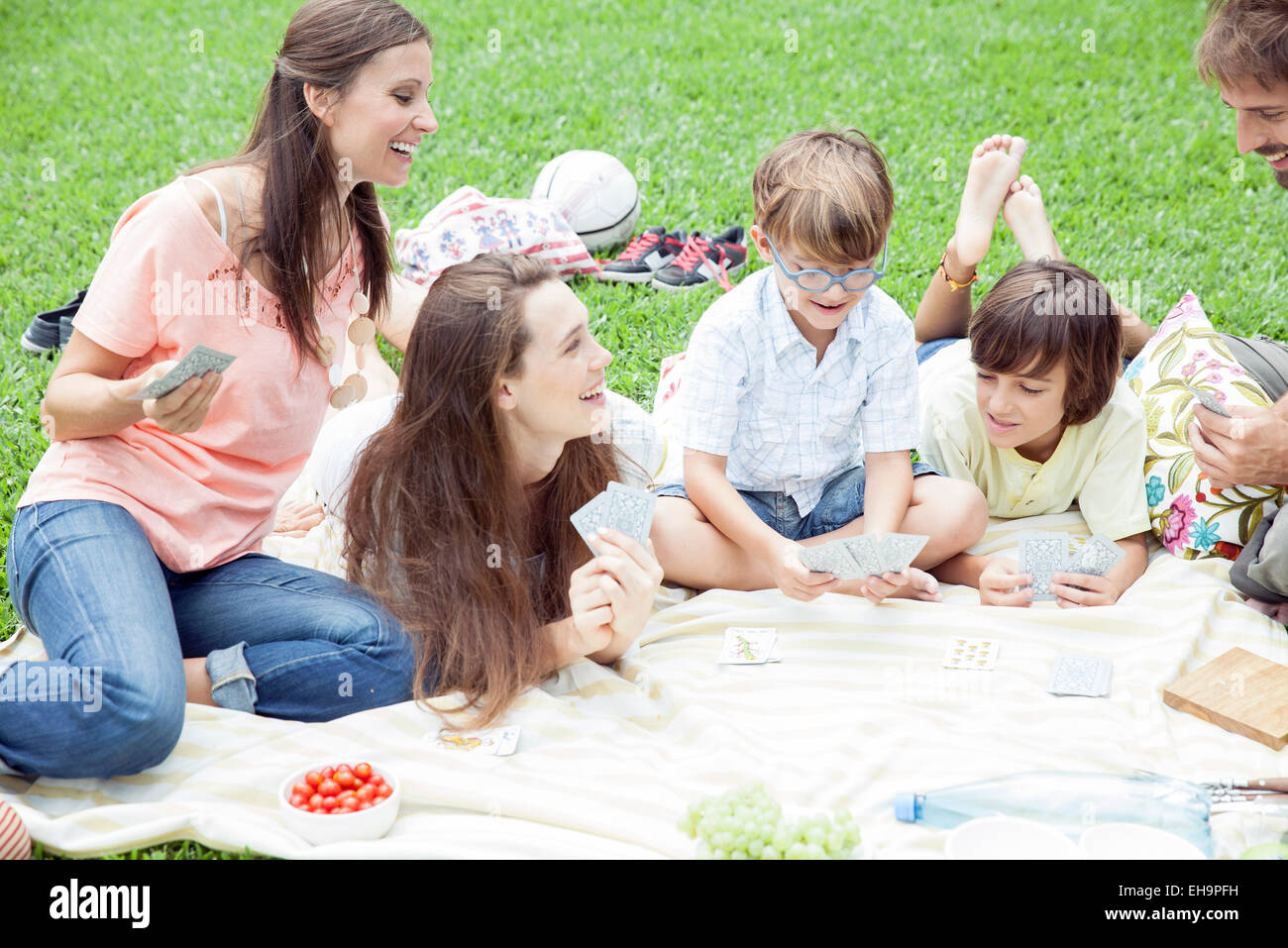 Family having picnic and playing card game - Stock Image