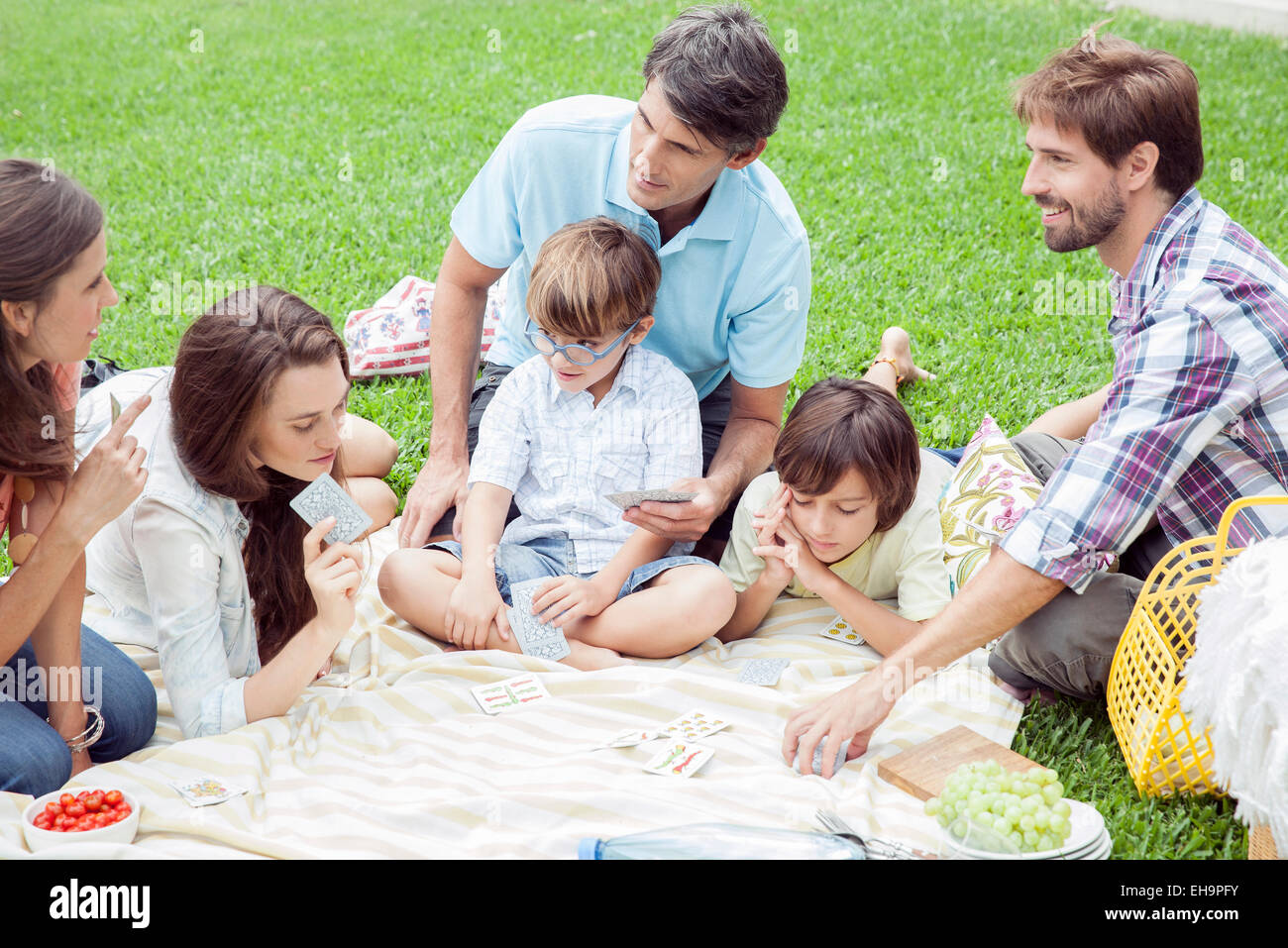 Family playing card game at picnic - Stock Image