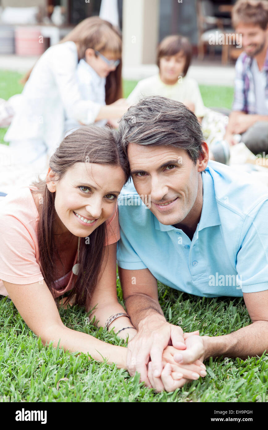 Couple lying side by side holding hands, portrait - Stock Image