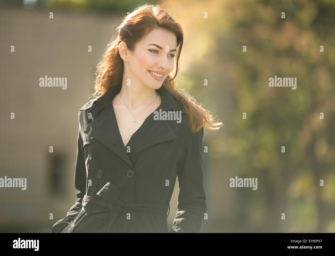 fashionable lady looking down in trench coat autumn time outdoors - Stock Image