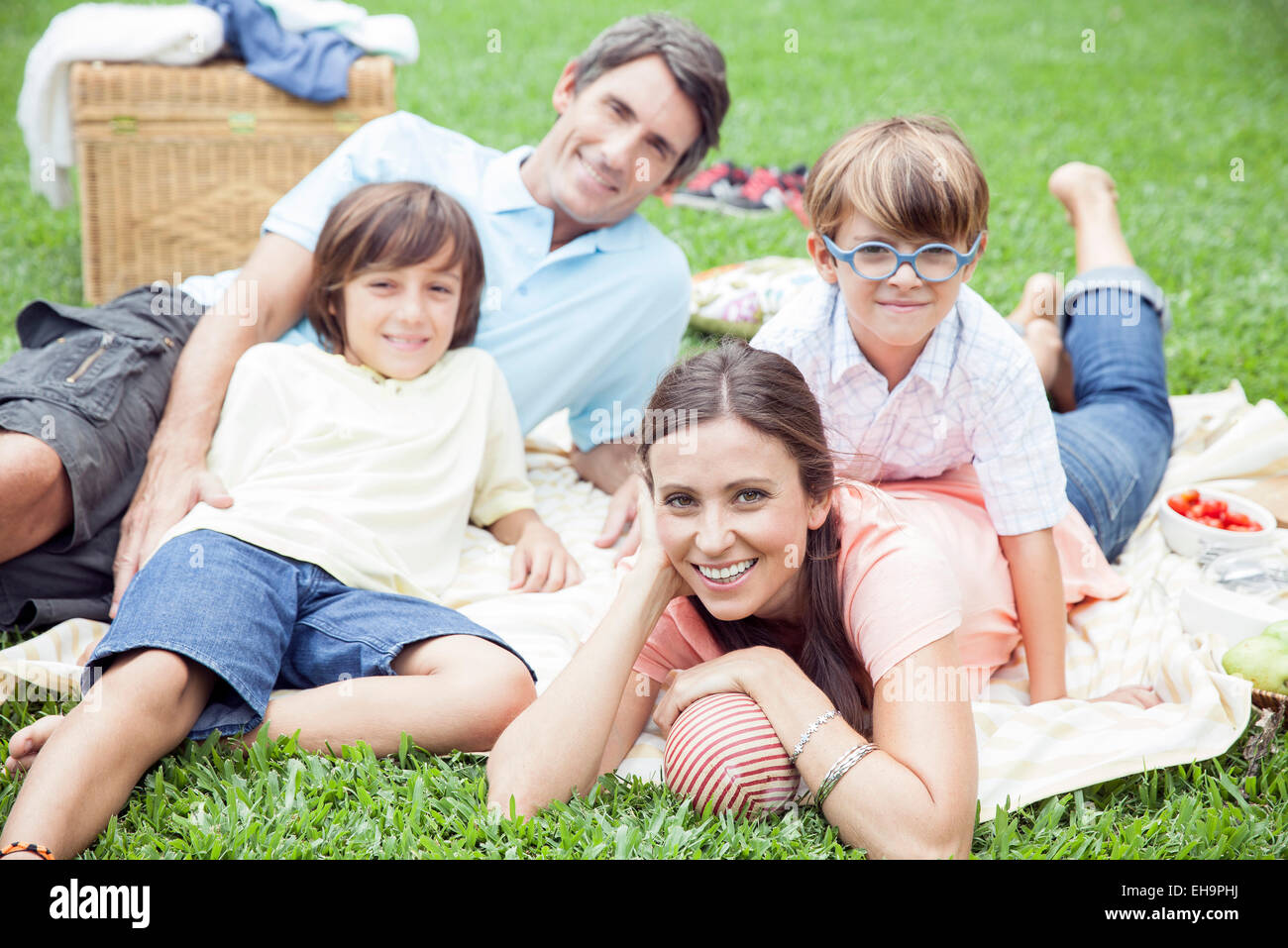 Family relaxing after picnic lunch at the park - Stock Image