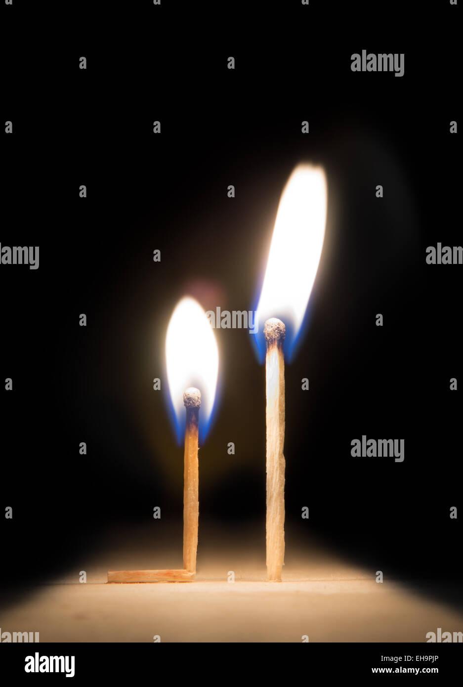 burning match kneeling before match on fire metaphor on black background - Stock Image