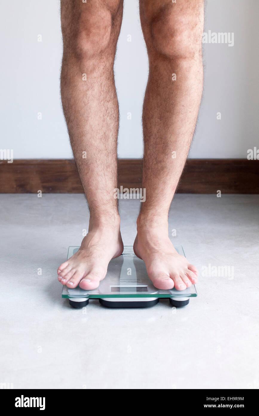 Man weighing self on bathroom scale - Stock Image