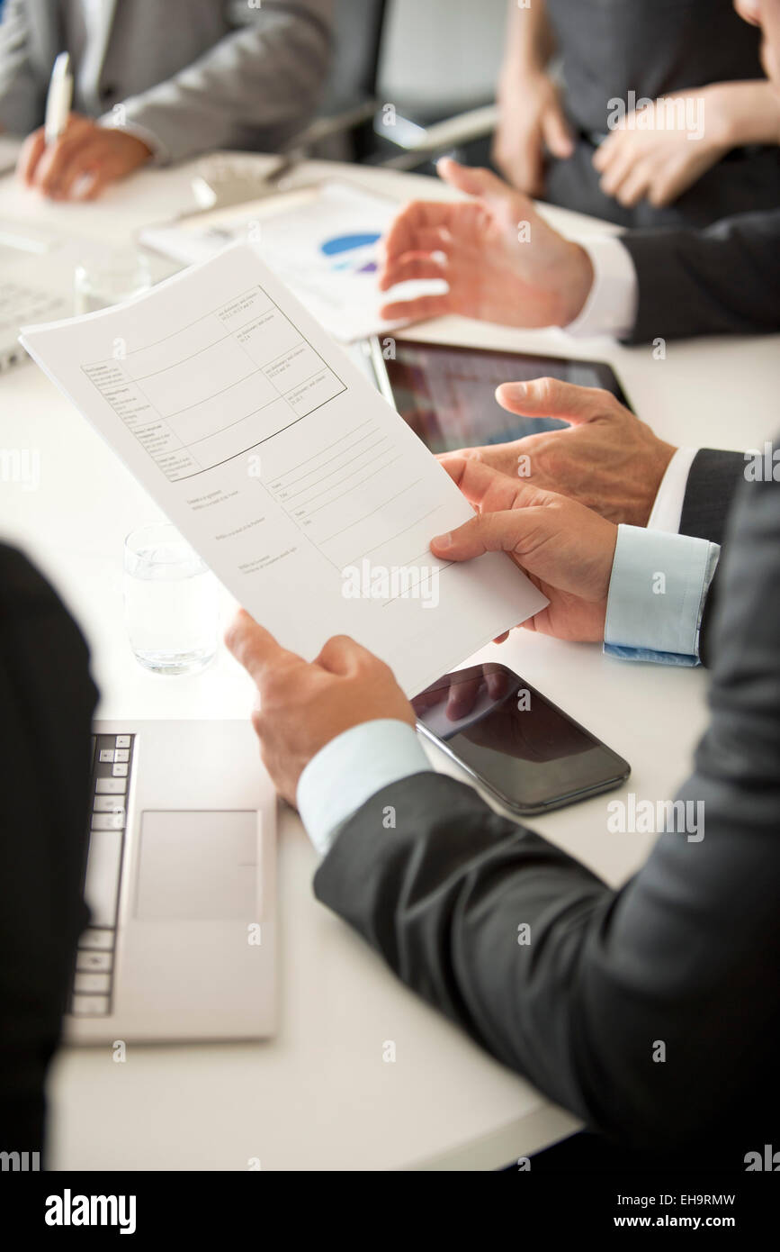Businessman at meeting reviewing document - Stock Image