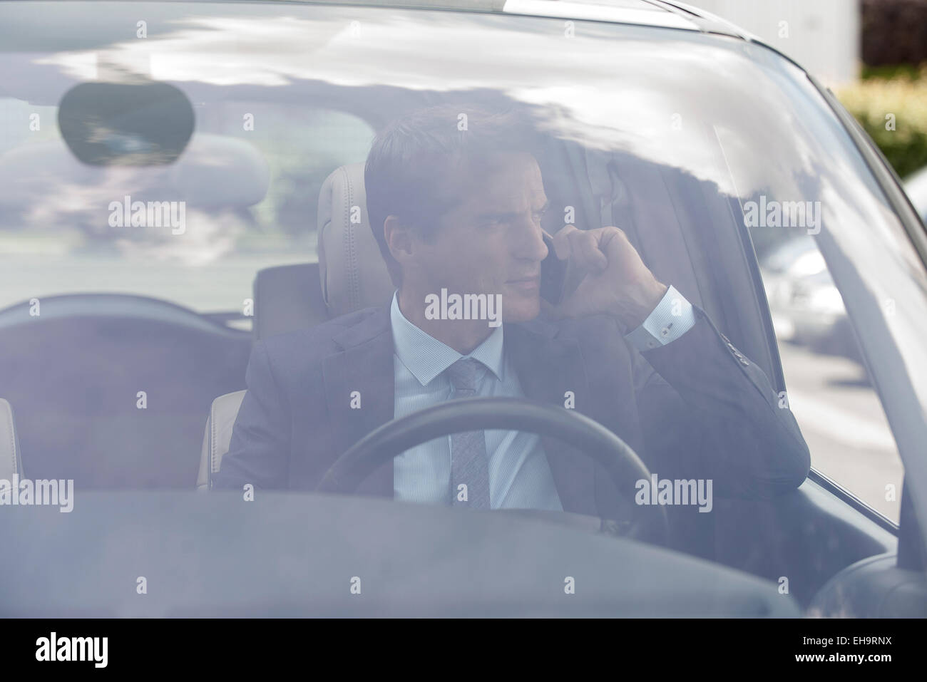 Businessman talking on cell phone in car - Stock Image