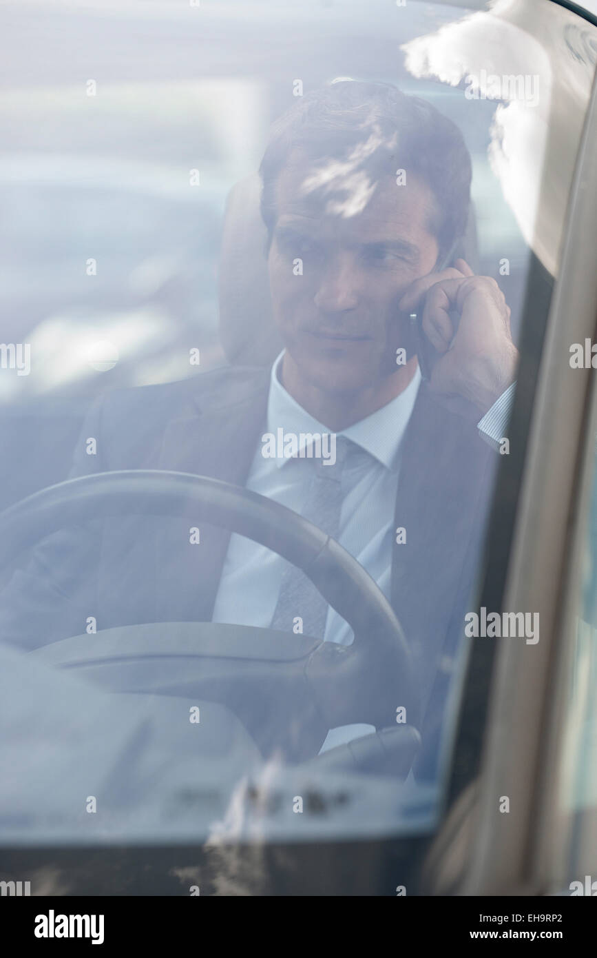 Businessman talking on cell phone while driving - Stock Image