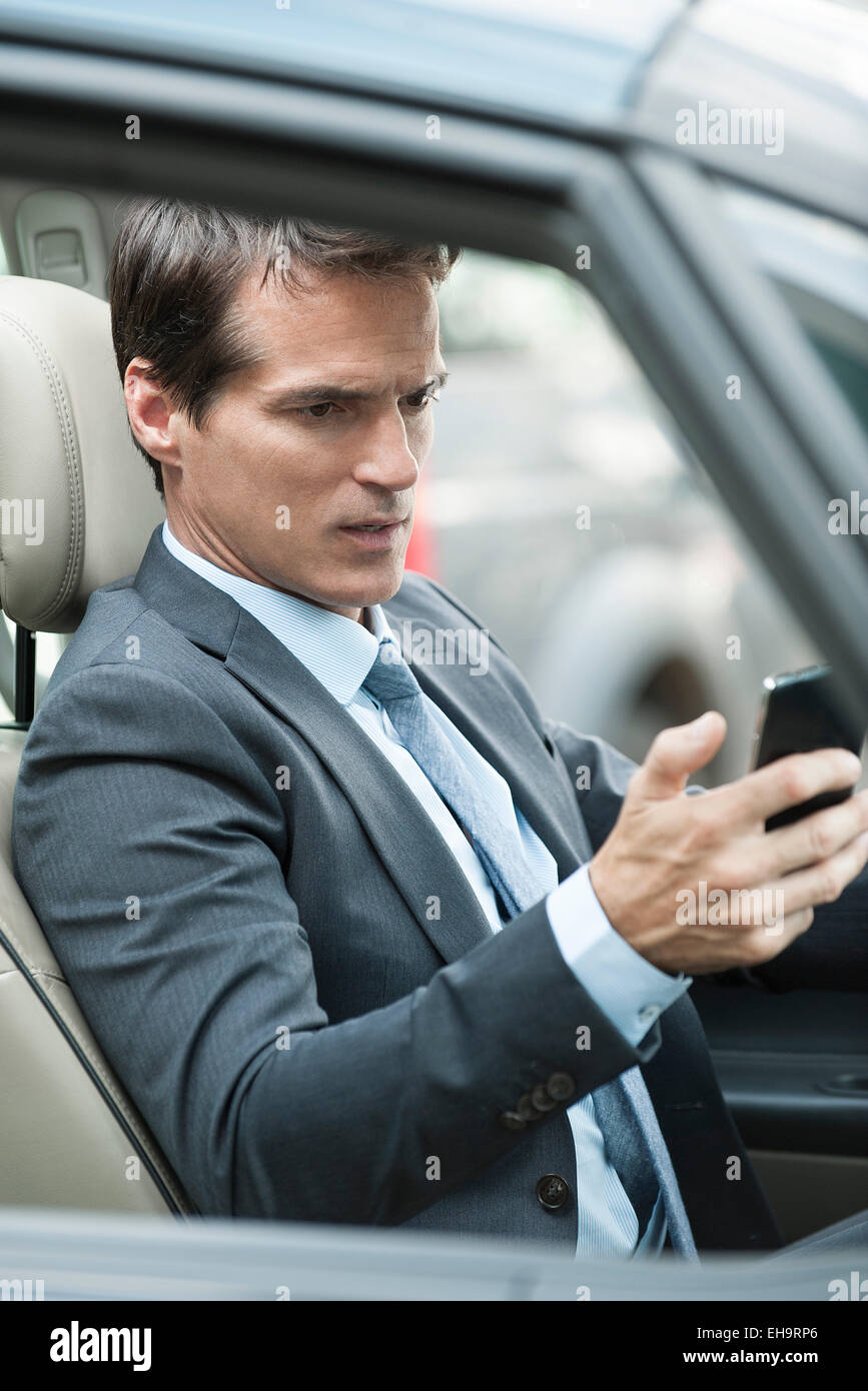 Man reading text message while driving - Stock Image
