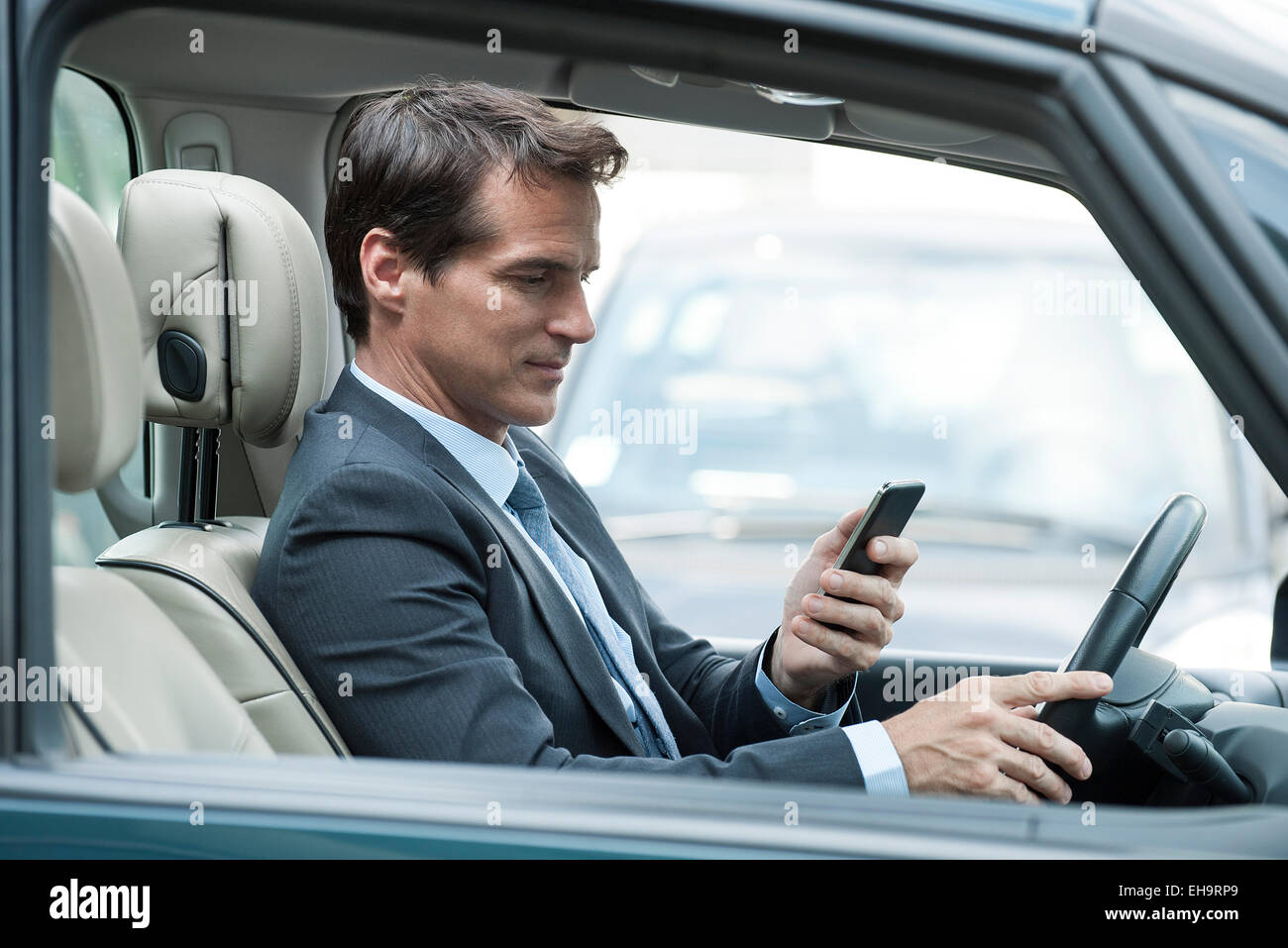 Man looking at cell phone while driving - Stock Image