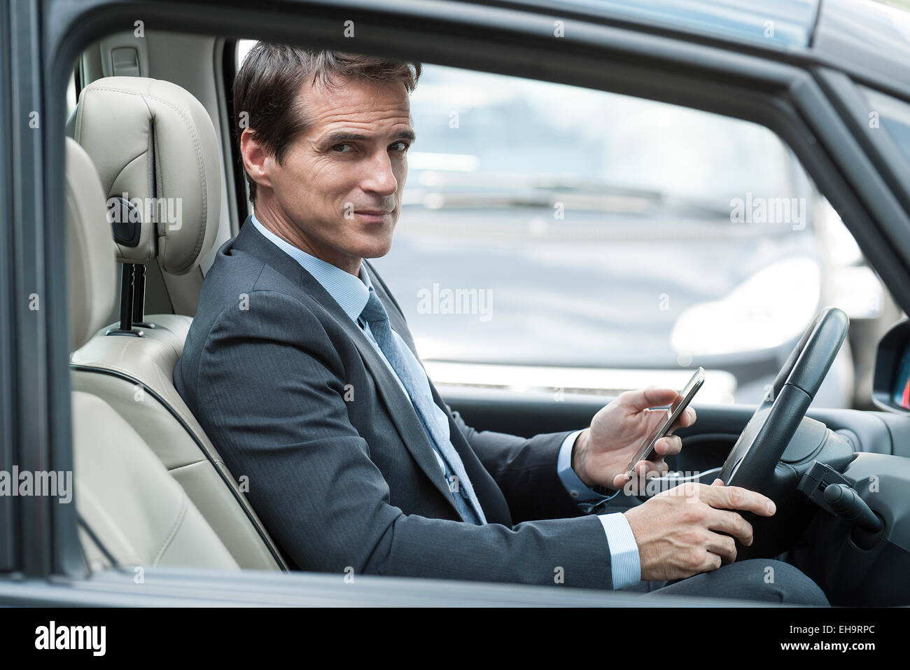 Man texting while driving car - Stock Image