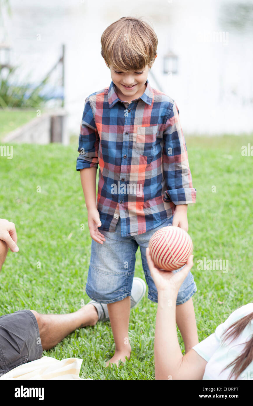 Boy playing ball at lakeside park with family - Stock Image