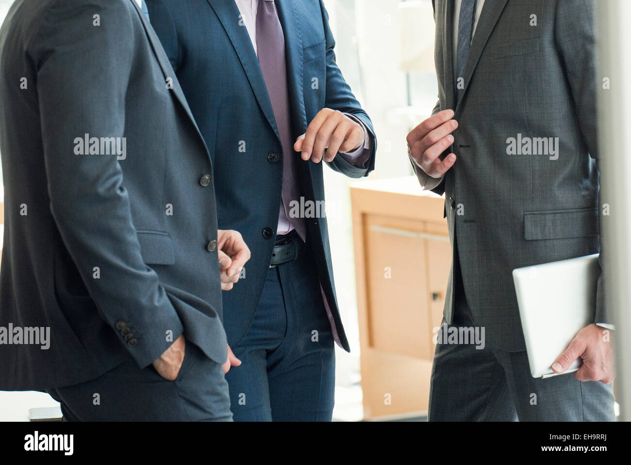Businessmen standing chatting before meeting - Stock Image