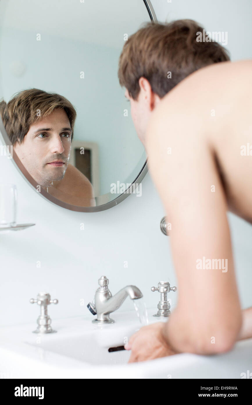 Man washing face in bathroom sink looking at self in mirror - Stock Image
