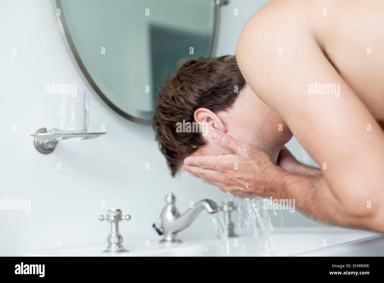 Man washing face in bathroom sink - Stock Image