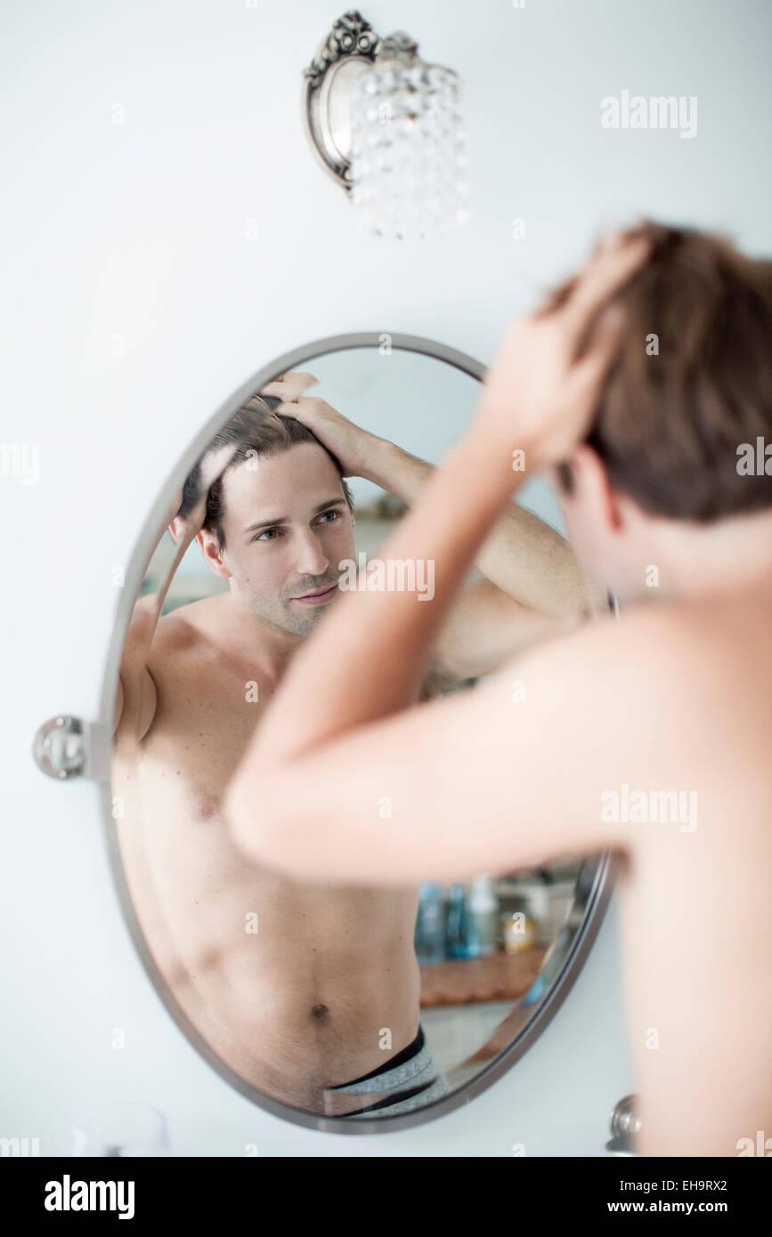 Man examining hairline in mirror - Stock Image
