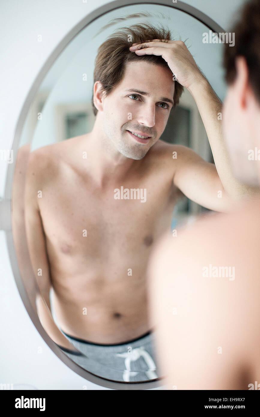 Man scrutinizing hairline in mirror - Stock Image