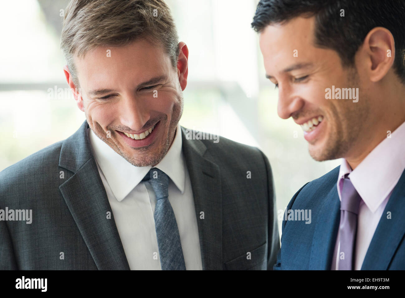 Businessmen talking and laughing together - Stock Image