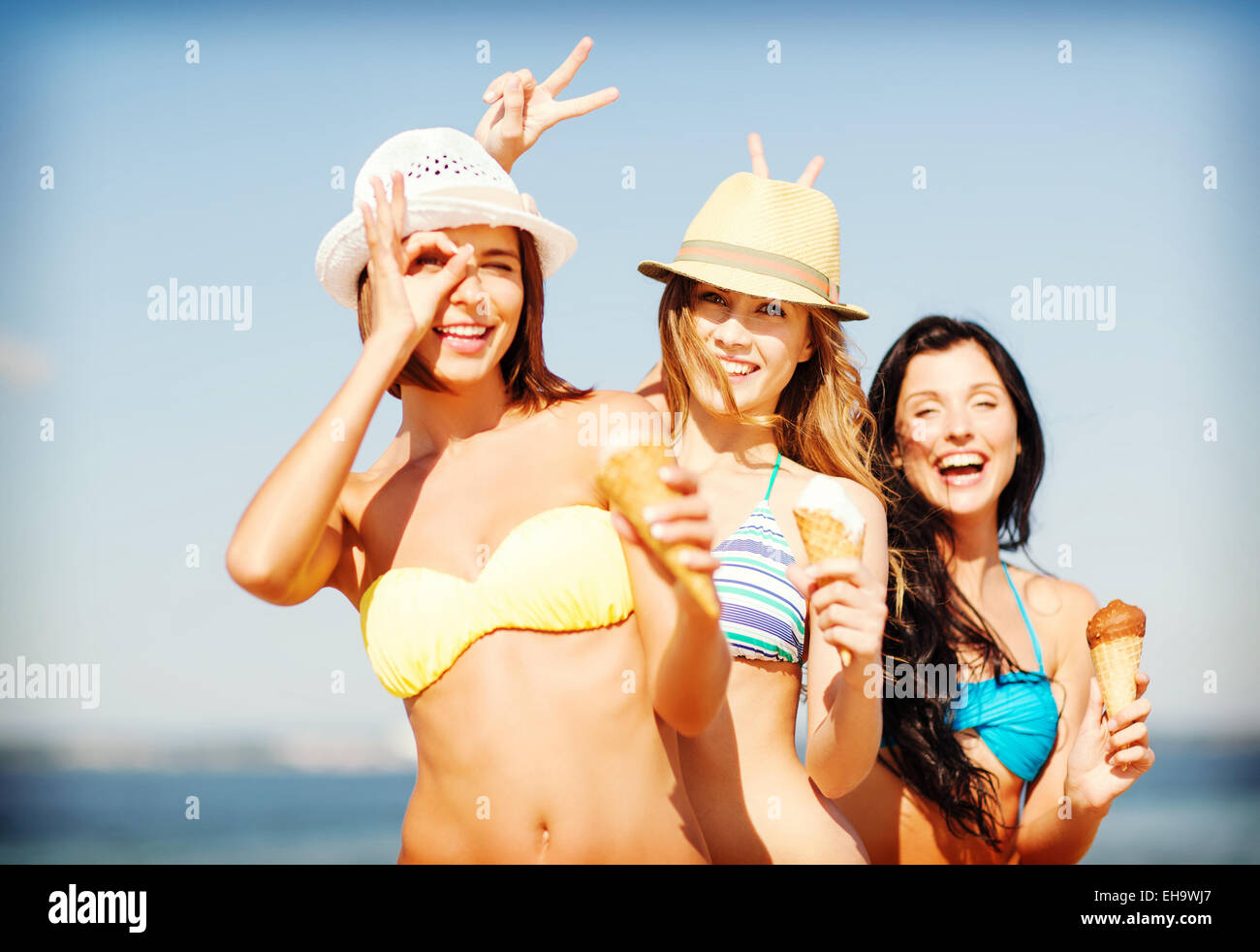 girls in bikini with ice cream on the beach Stock Photo