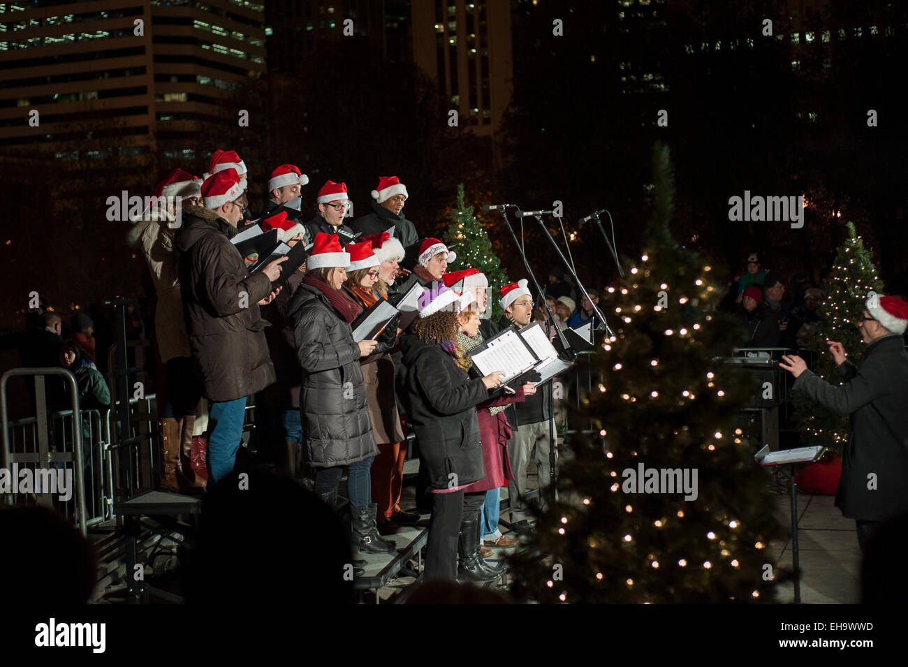 Chicago, USA. A choir sing Christmas carols at night by Cloud Gate ...