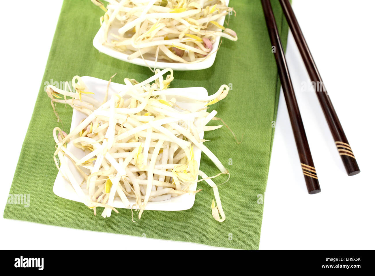 bright mung bean sprouts with chopsticks on a light background - Stock Image