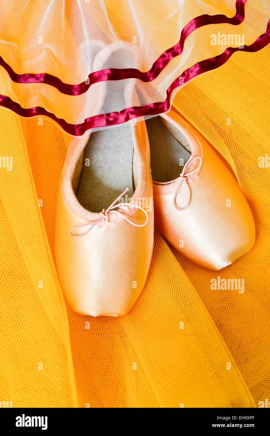 Pair of pointe shoes on yellow tutu - Stock Image