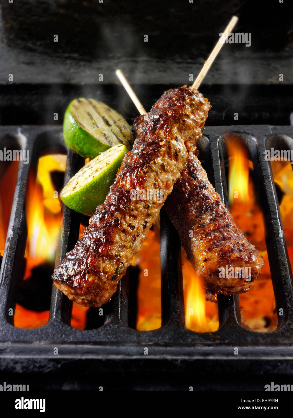 Lamb kofta kebabs being cooked over hot charcoal flames - Stock Image