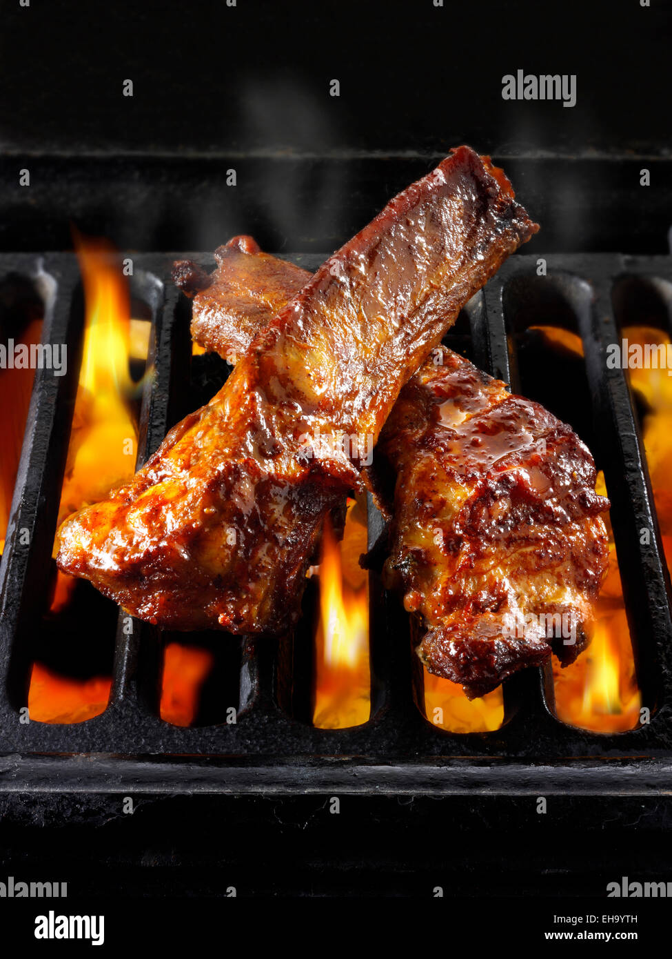 Barbecue spare ribs being cooked over open flames - Stock Image