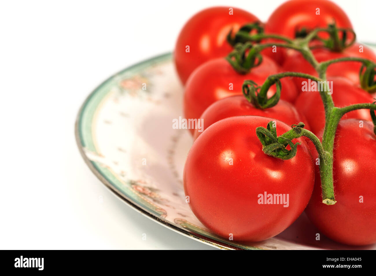Plate of ripe tomatoes on the vine - Stock Image