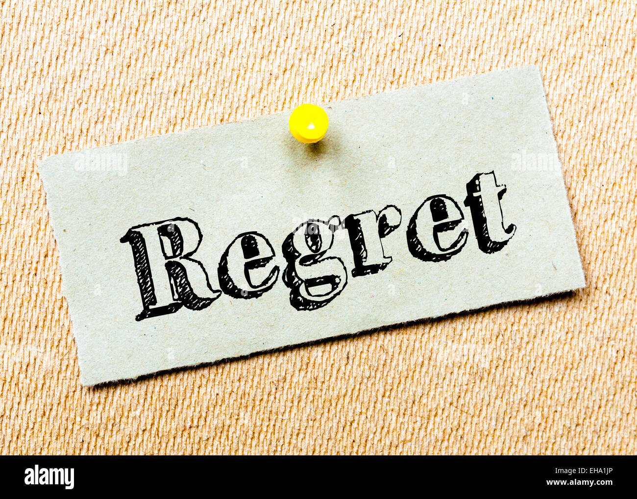 Recycled paper note pinned on cork board. Regret Message. Concept Image - Stock Image