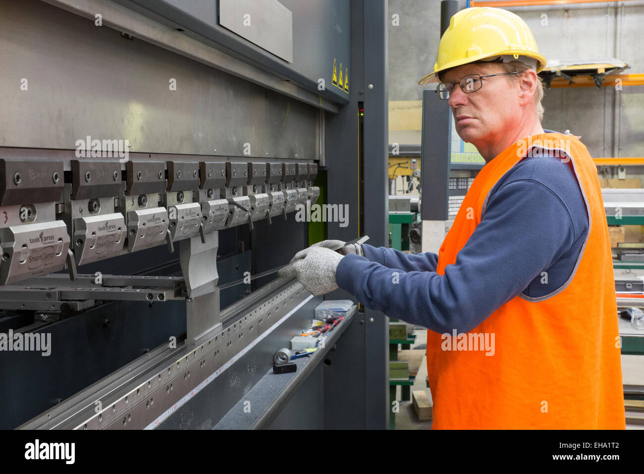 metal industry worker operates CNC brake press machine Stock Photo
