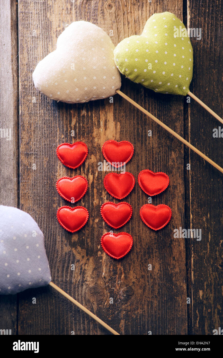 different types of fabric hearts on wooden background. Valentine's day - Stock Image