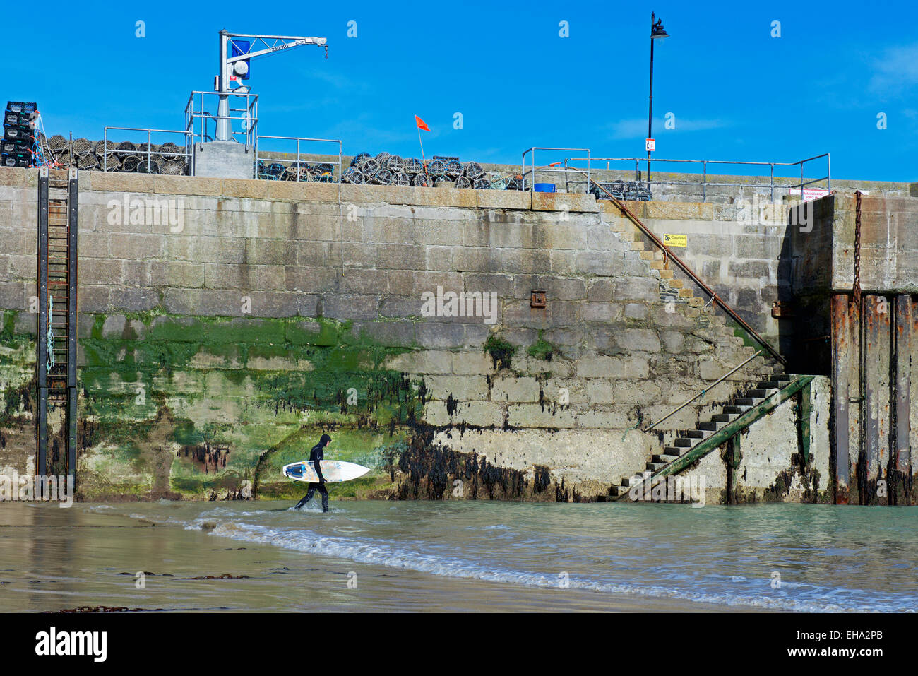 Surfer walking through the harbour at Newquay, Cornwall, England UK - Stock Image