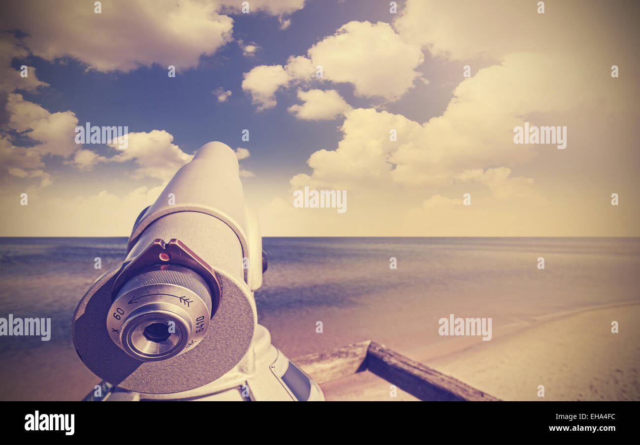 Retro toned picture of telescope on a beach pointed at beautiful sky. - Stock Image
