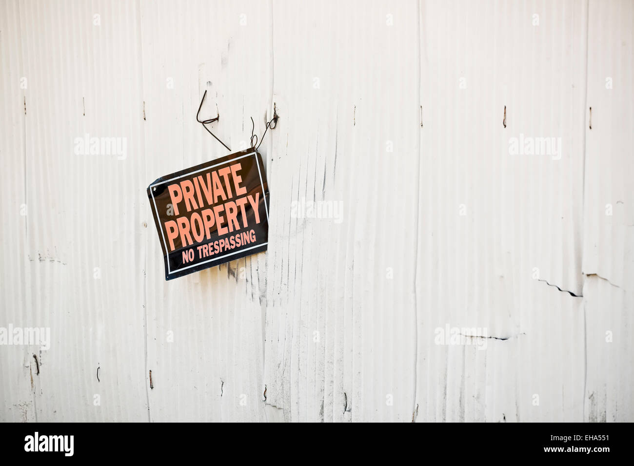 Private Property No Trespassing sign loosely attached to a metal building - Stock Image