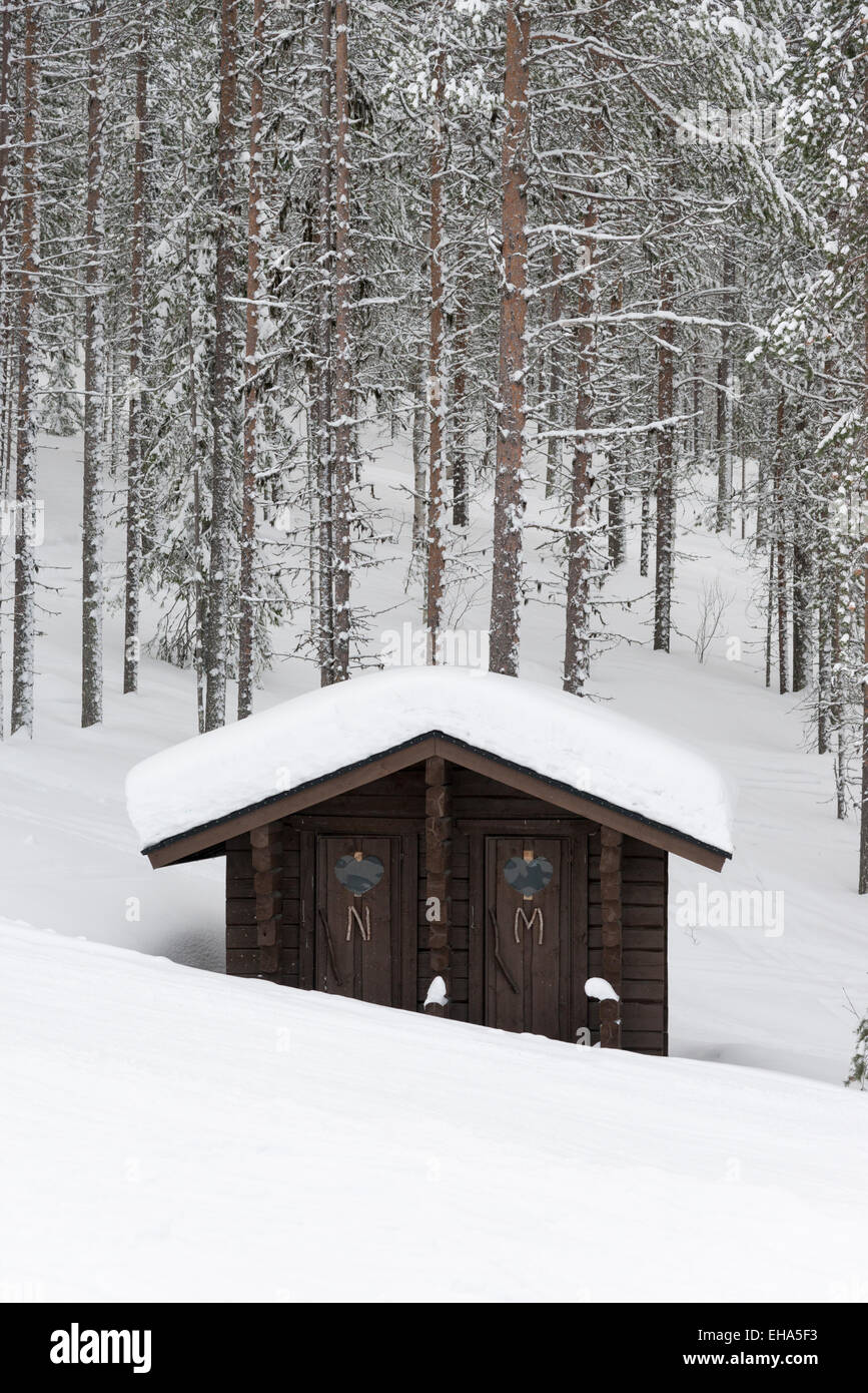 Toilets in wooden shed on the side of the piste at the ski resort of Levi Lapland Finland in the snow. - Stock Image