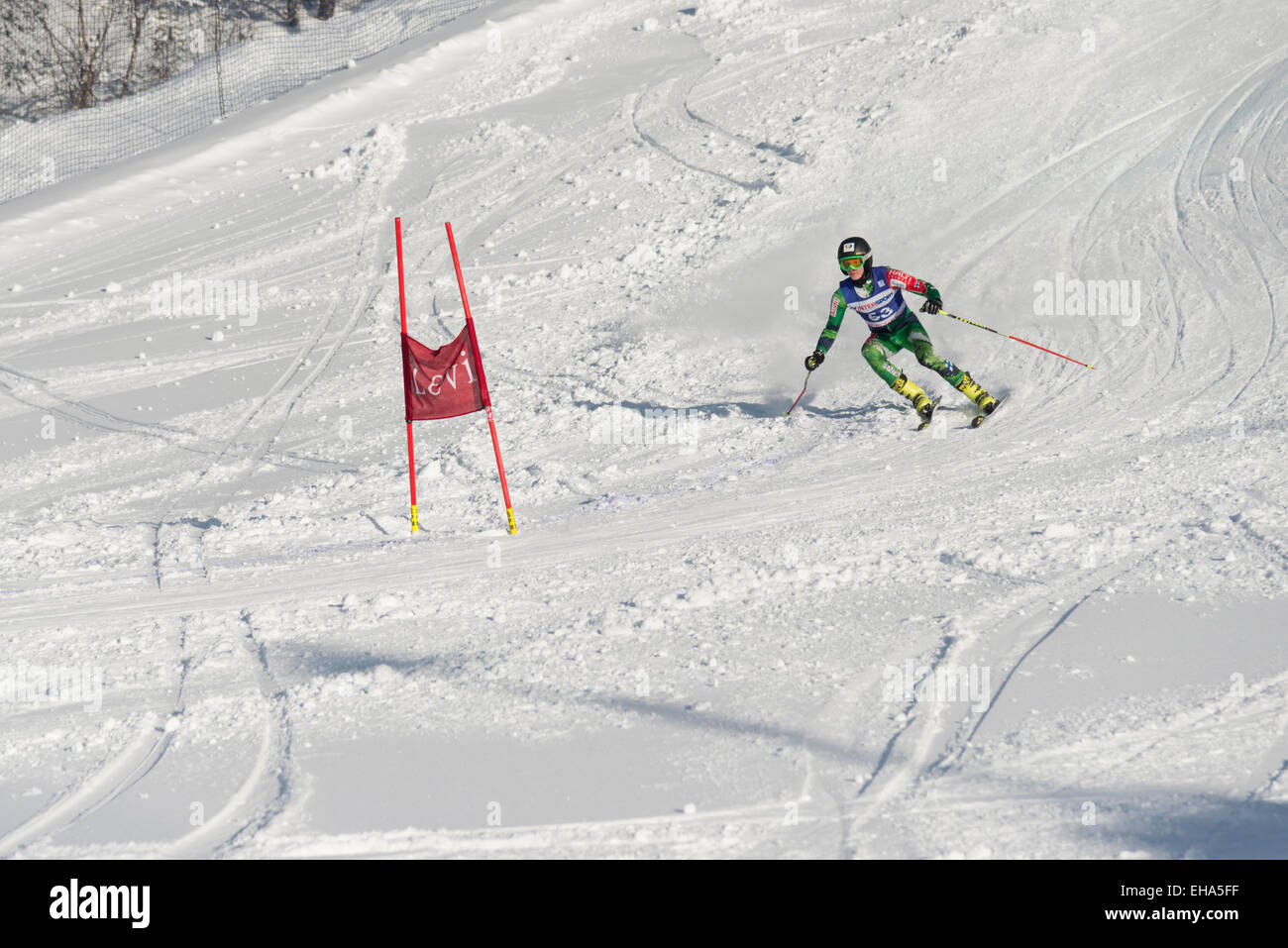 A giant slalom skier racer approaching a gate on a piste at Levi Finland - Stock Image