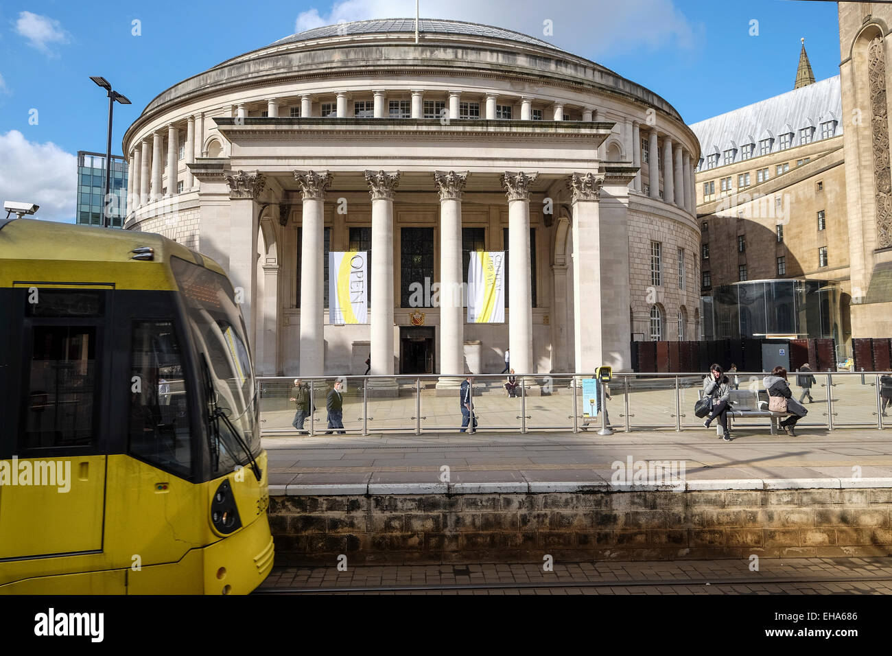 Manchester England: A Metro-link tram approaches the station by the City's Central Library building - Stock Image